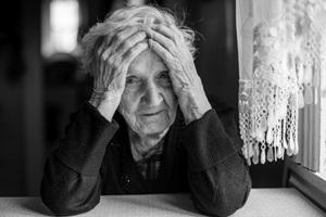 elderly woman holding her head in confusion Gray & White