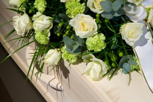 white flowers on top of white casket at funeral