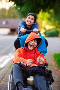 girl pushing brother with cerebral palsy in wheelchair