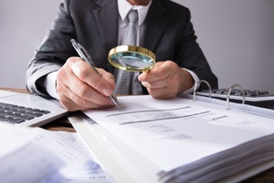 investigator looking at files with magnifying glass