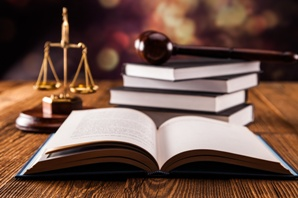 legal book open on table with scales of justice and gavel