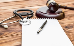 legal pad with judge's gavel and stethoscope