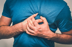 man having heart attack clutching his chest