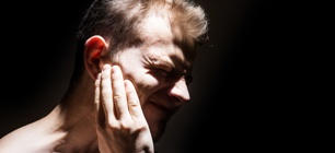 man-holding-ear-in-pain-black-background