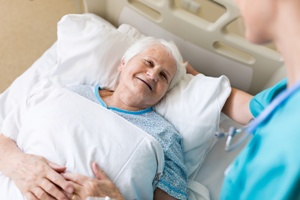nursing home resident in bed talking to staff member