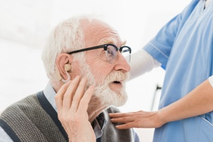 nursing home resident with hearing aid talking to staff member