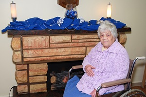 A nursing home resident sits dangerously close to the fireplace