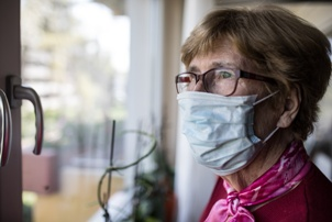 older woman wearing mask in nursing home