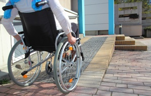 person in wheelchair approaching wheelchair ramp to home