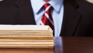 pile of folders in front of man in suit
