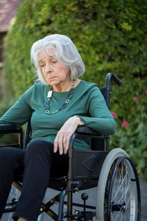 sad woman in wheelchair nursing home neglect