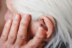 senior adjusting hearing aid in ear