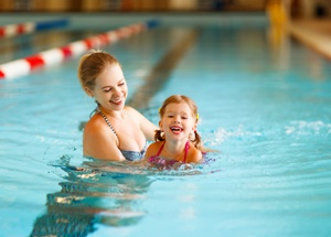 swim teacher in pool with young child