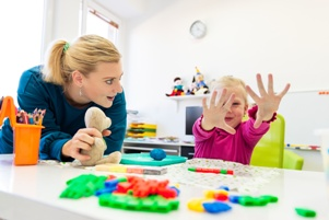 teacher and small child in play therapy session