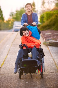 teen girl pushing teen boy with cerebral palsy in wheelchair
