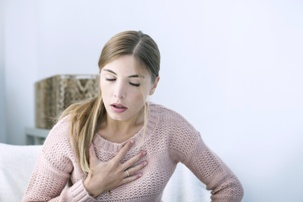 young woman having asthma attack clutching chest