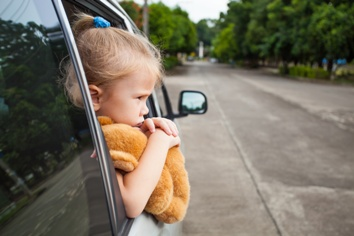 Child Looking Out of the Backseat Window in a Car