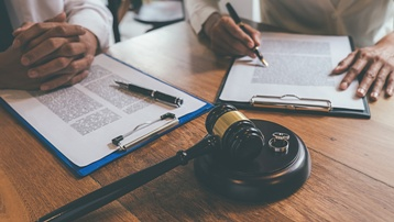 Divorce Paperwork With a Gavel and Rings