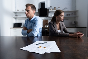Divorcing Couple With Paperwork and Weddings Rings on the Table
