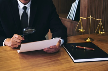 Man Holding a Magnifying Glass in a Lawyer's Office