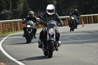 Three Motorcyclists Lane Sharing on a Local Road