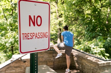 Man Crossing Fence Behind a No Trespassing Sign