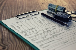 Auto Insurance Paperwork With Car Key and Money