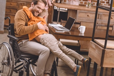 Disabled Father in Wheelchair Hugging His Son