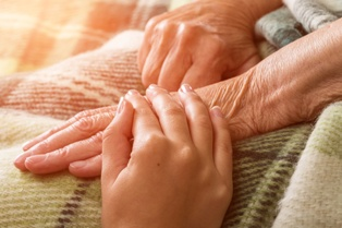 Holding an Elderly Resident's Hand in a New Mexico Nursing Home