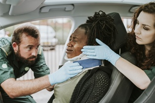 Injured Passenger Being Cared for After a Car Wreck