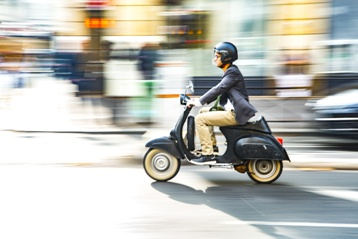 Man Driving a Moped Down the Street