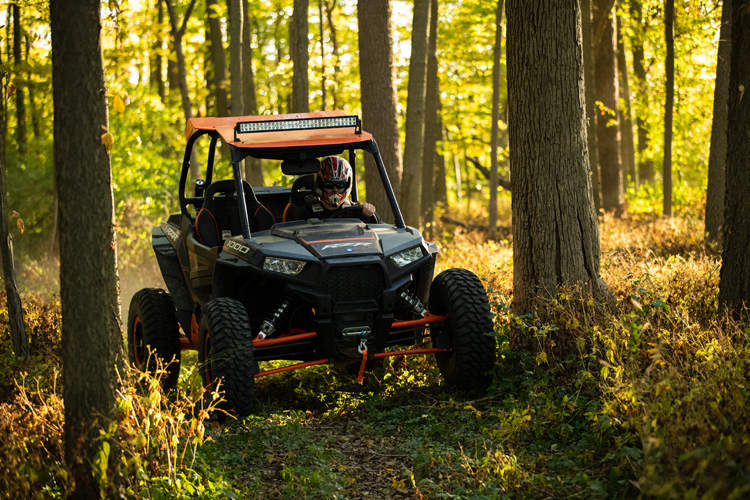 A driver operating a Polaris RZR--which has been recalled for fire hazards--in the woods.