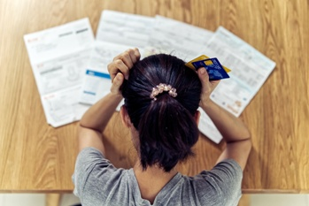 Woman Looking at Bills in a Worried State