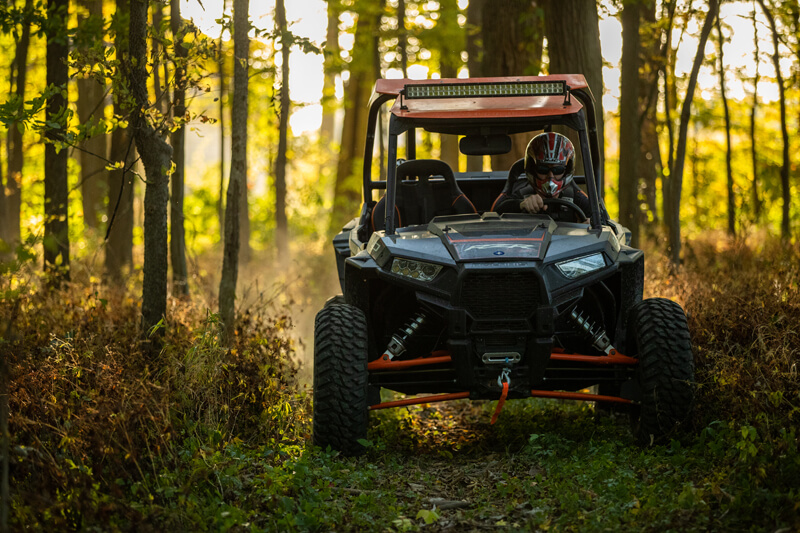 A Polaris RZR ATV being driven in the woods.