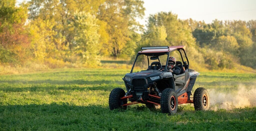 A man driving the Polaris RZR side x side.