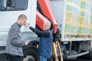 An insurance adjuster examines a truck recently involved in a collision