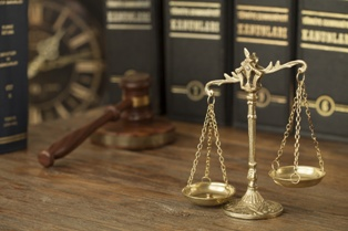 Law Books, Scales of Justice, and Wooden Gavel on a Lawyers Bookshelf