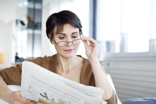 A Woman Reading a Newspaper About Reckless Driving Charges