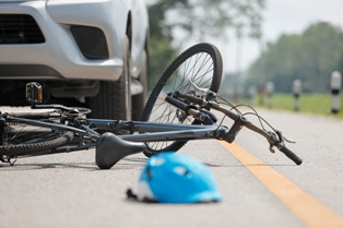 Bicycle Laying on the Ground in Front of a Vehicle After an Accident