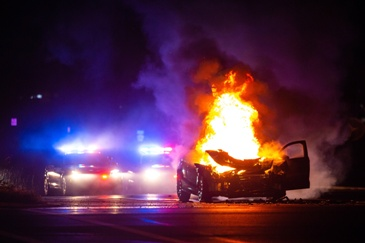 Car Engulfed in Flames in the Middle of the Road