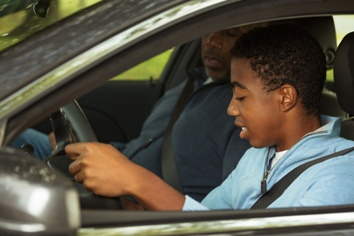 Father Teaching His Teenage Son How to Drive