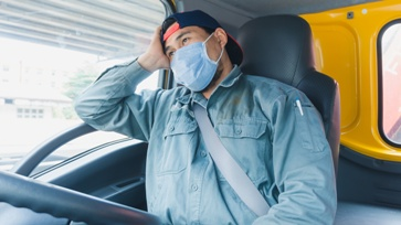 Truck Driver With Mask on Sitting in the Cab