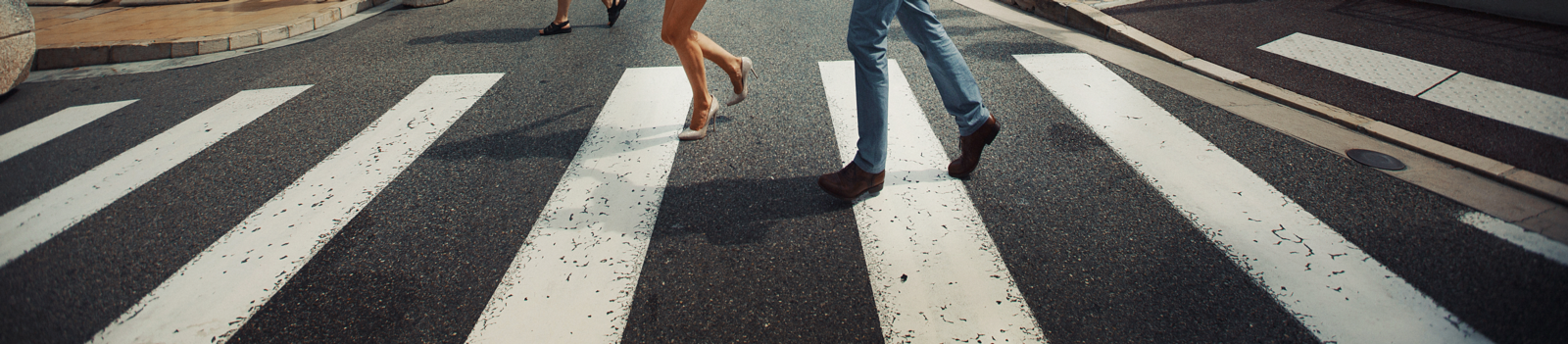 white cross walk with a man in jeans and a woman in heels crossing the road