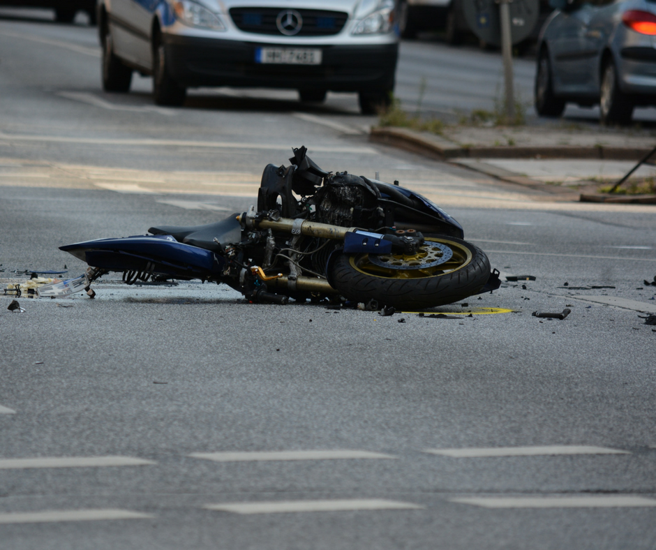 Black Motor Cycle crashed into pieces in roadway intersection