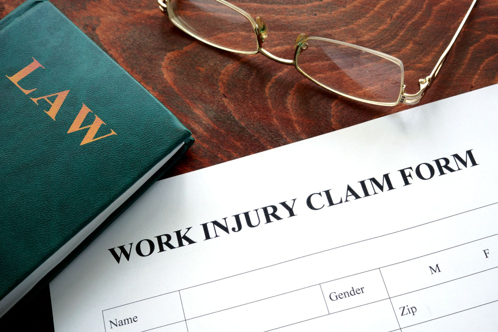 Iowa Work Injury Claim Form with glasses and a green law book