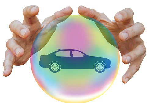 Hands around bubble containing car