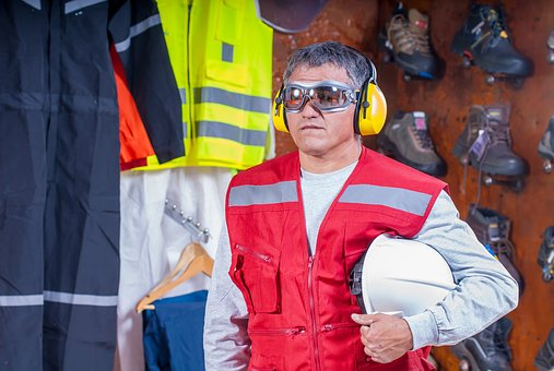 Construction work wearing proper eye and ear protection gear holding helmet