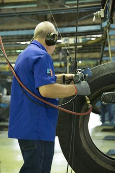 Factory worker in shirtsleeve blue shirt working on tires