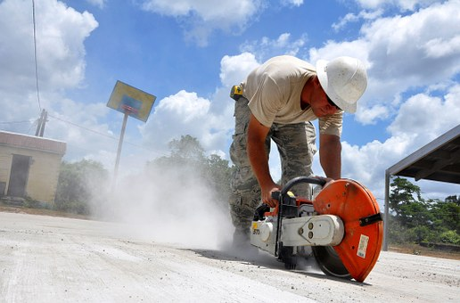 Construction worker cutting cement in summer
