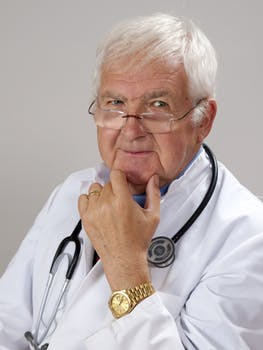 Male Independent medical examiner doctor scratching chin